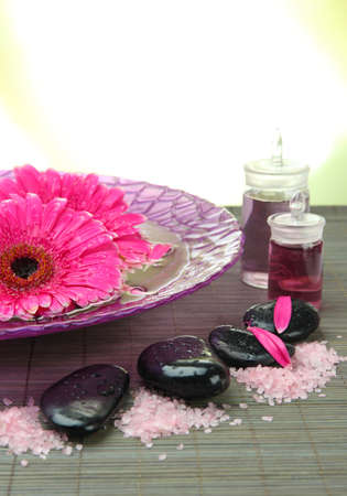 Gerbera flowers on water and spa stones on bamboo mat, isolated on white photo