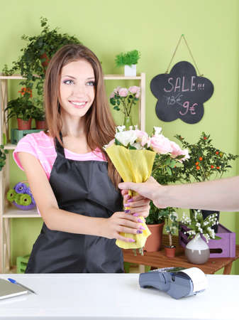 Beautiful girl florist with flowers in flowers shop photo