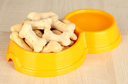 Dry dog food in bowl on wooden background photo