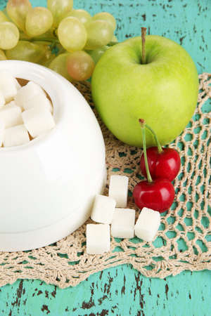 fructose: Refined sugar in white sugar bowl on wooden background