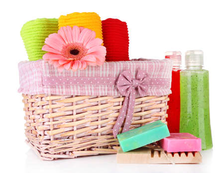 Colorful towels in basket, cosmetics bottles and soap, isolated on white photo