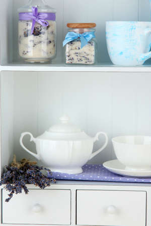 Still life with jar of lavender sugar, cup and fresh lavender flowers on shelves photo