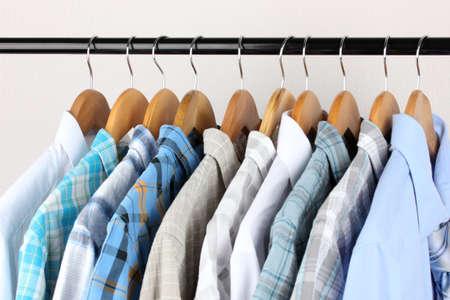 tienda de ropa: Las camisas con lazos en perchas de madera sobre fondo claro