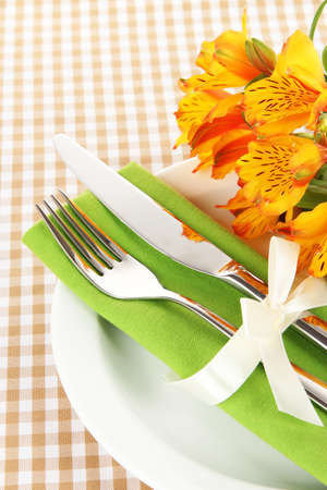 alstromeria: Festive dining table setting with flowers on checkered background Stock Photo