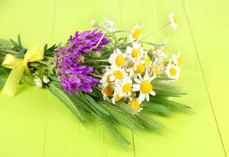 Wild flowers and green spikelets, on wooden background photo