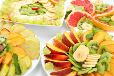 Assortment of sliced fruits on plates, close up photo