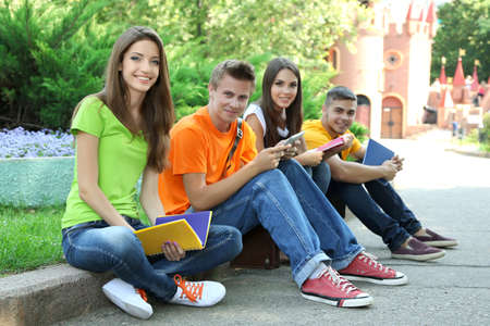 Happy groupe de jeunes étudiants assis dans le parc