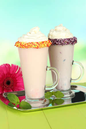 Delicious milk shakes on table on light background photo