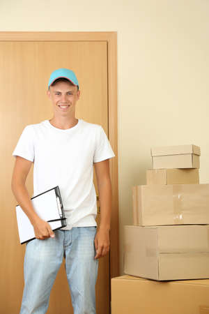 Young delivery man with parcels and clipboard, Stock Photo - 21554015