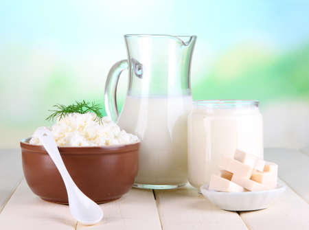 pasteurized: Fresh dairy products on wooden table on natural background