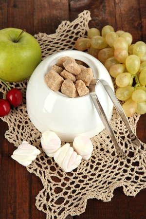 Unrefined sugar in white sugar bowl on wooden background photo