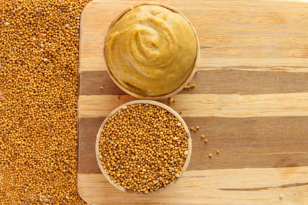 Mustard with seeds on wooden background