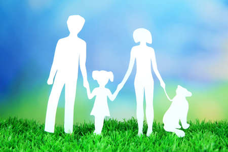 Family from paper on grass on bright background photo