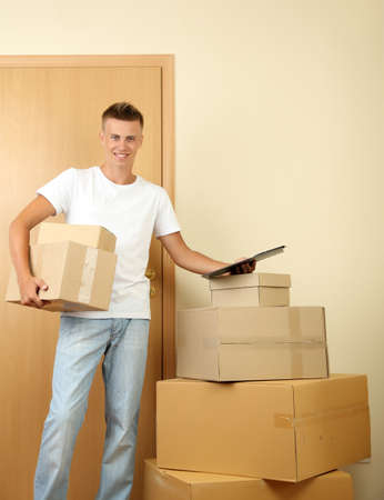 Young delivery man with parcels and clipboard, Stock Photo - 21554098