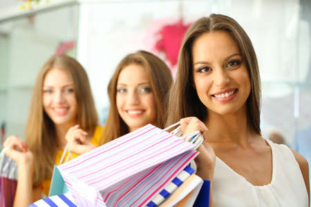 Three beautiful young woman in shop with shopping bags photo