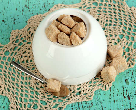 unrefined: Unrefined sugar in white sugar bowl on wooden background
