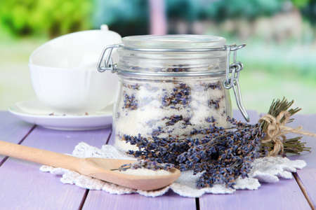 Jar of lavender sugar and fresh lavender flowers on bright background