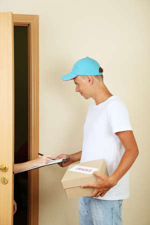 Young delivery man giving parcel Stock Photo - 21554557