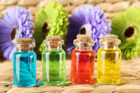 liquids: Bottles with colored liquids on  wicker wooden background Stock Photo