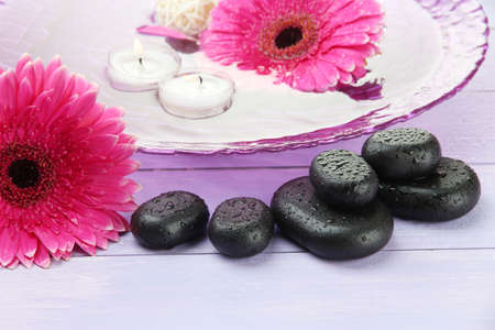 Spa stones, beautiful gerbera flowers and candles on water photo