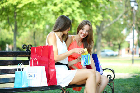 Two beautiful young woman with shopping bags in park photo