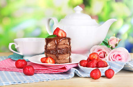 Chocolate cake with strawberry on wooden table on natural background photo