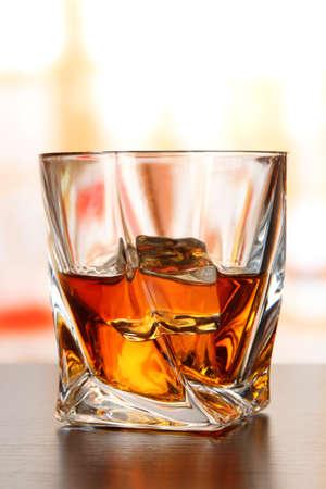 whiskey bottle: Glass of whiskey, on bright background