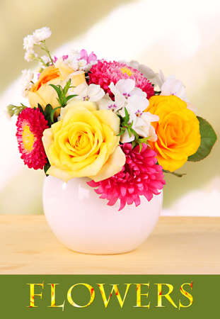 Beautiful bouquet of bright flowers in vase on bright background photo