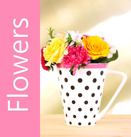 Beautiful bouquet of bright flowers in mug on bright background photo