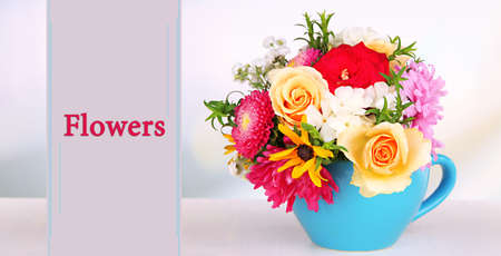 Beautiful bouquet of bright flowers in blue mug on light background photo