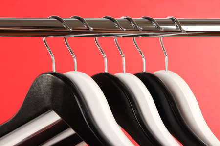 Black and white clothes hangers on color background photo