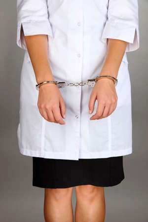 Doctor in handcuffs on grey background photo