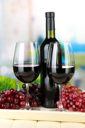 Ripe grapes, bottle and glasses of wine on tray, on bright background Stock Photo - 21556159
