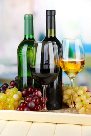 Wine bottles and glasses of wine on tray, on bright background Stock Photo - 21556161