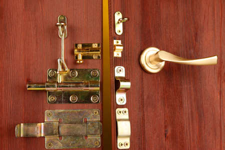 deadbolt: Metal bolts, latches and hooks in wooden open door close-up