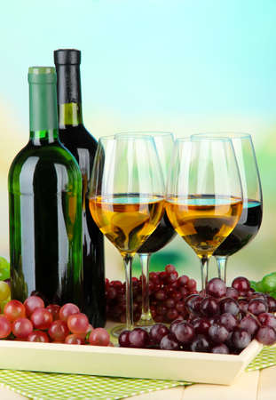 Wine bottles and glasses of wine on tray, on bright background Stock Photo - 21556229