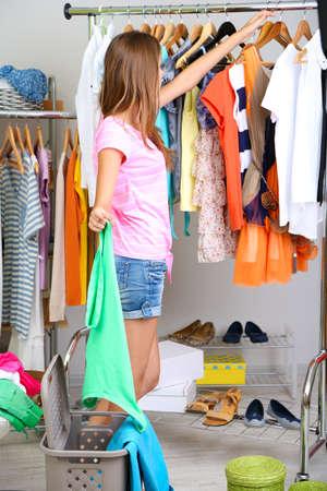 vestidos antiguos: Hermosa ni�a tira la ropa innecesarios en la habitaci�n Foto de archivo