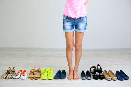 sandals: Girl chooses shoes in room on grey background
