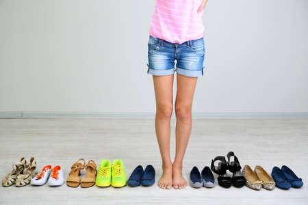 comprando zapatos: La muchacha elige los zapatos en la sala sobre fondo gris