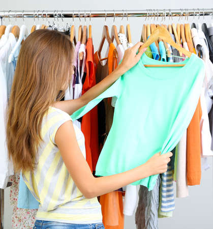 female clothing: Beautiful young woman  thinking what to dress near rack with hangers