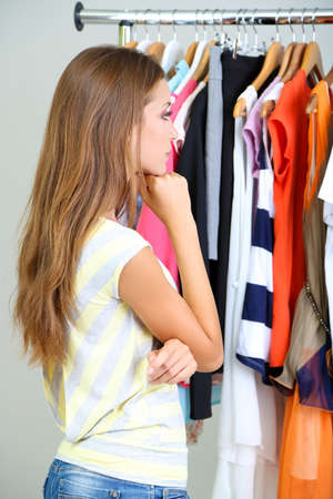 Beautiful young woman  thinking what to dress near rack with hangers photo