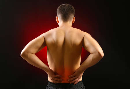 Lower back pain in man on dark background photo