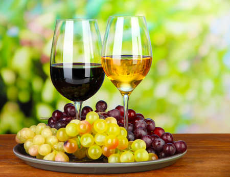 Ripe grapes and glasses of wine, on bright background Stock Photo - 21556322