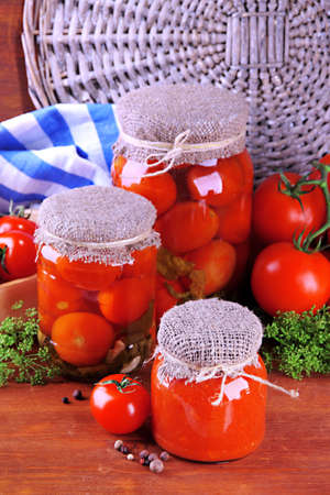 Tasty canned and fresh tomatoes on wooden table photo