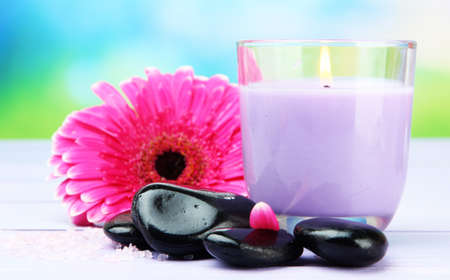 Spa stones, beautiful gerbera and candle on wooden table Stock Photo - 21663624