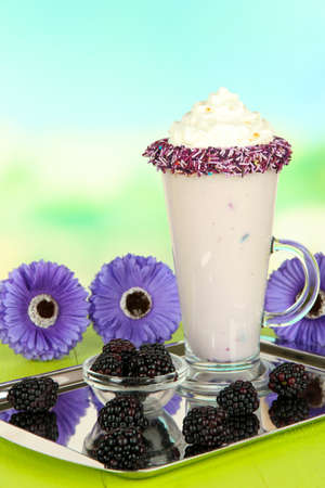 Delicious milk shake on table on light background photo