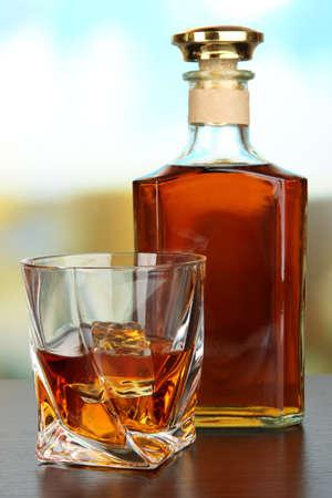 whisky bottle: Glass of whiskey with bottle, on dark background
