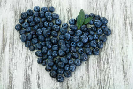 Heart of blueberries on wooden background photo