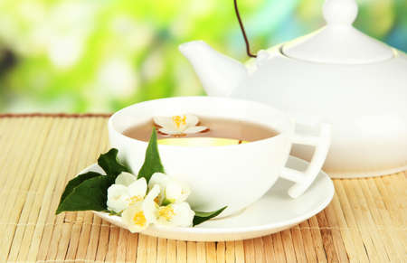 Cup of tea with jasmine, on bamboo mat, on bright background photo