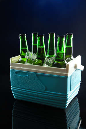 Bottles of beer with ice cubes in mini refrigerator, on dark blue background photo